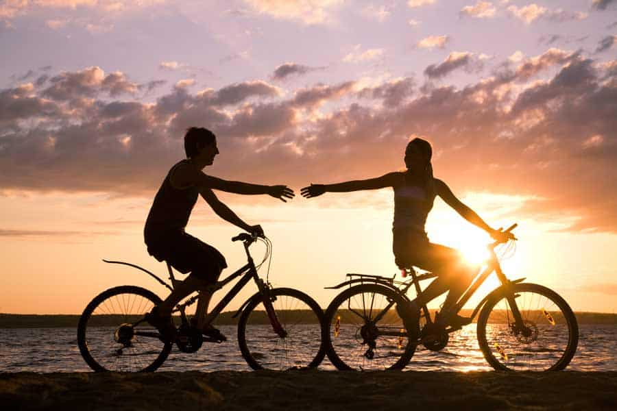 Couple riding bike in the sunset