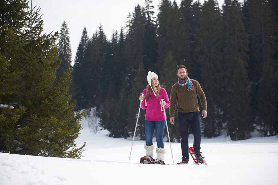 Couple snowshoeing in woods