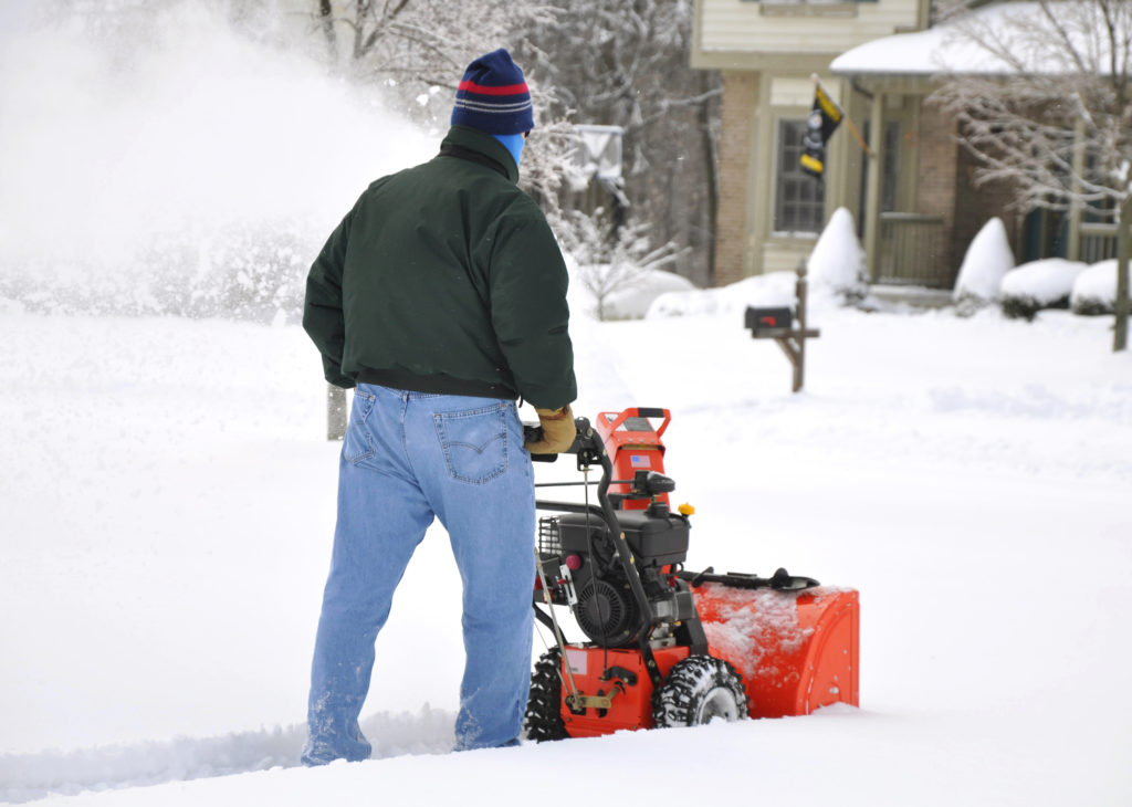 Man Using Snow Blower on Minnesota Sidewalk