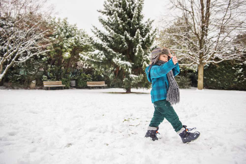 Boy Playing in Snow with Kids Snow Boots On