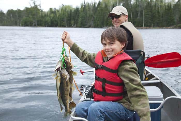 Man and boy fishing on lake
