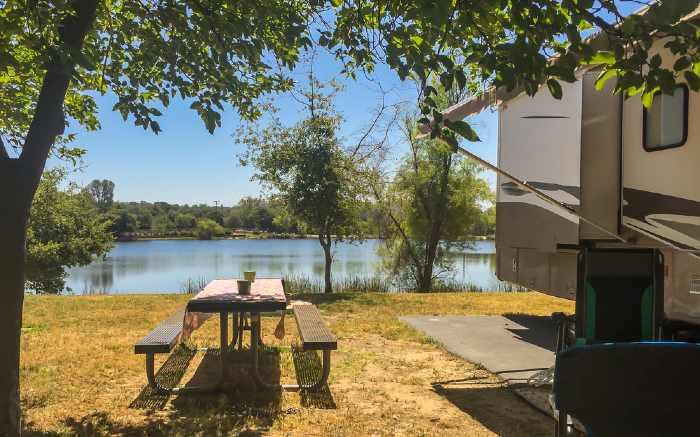 RV and picnic table at campground near lake.