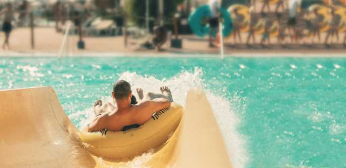 man going down a water slide in an innertube