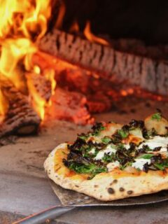 Kale pizza out of fire oven