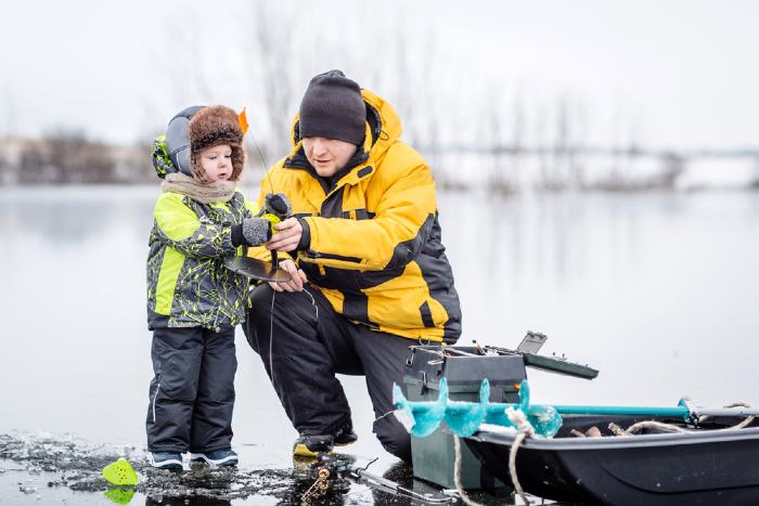 Father teaching his son how to fish on a frozen lake in winter.