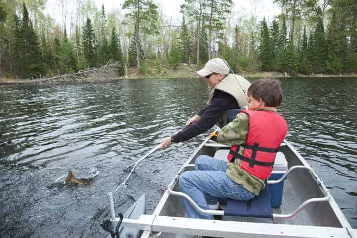 Man and boy fishing in canoe on lake