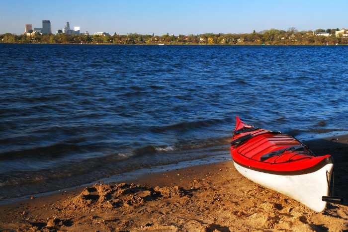Red kayak on lakeshore.
