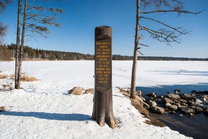 A view of an historical marker in Itasca State Park with snow on the ground.  Even in winter, Itasca State Park is one of the best places to visit in Minnesota.
