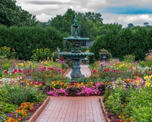 View of a fountain surrounded by flower beds at Clemens Garden in St. Cloud -- one of the best places to visit in Minnesota.