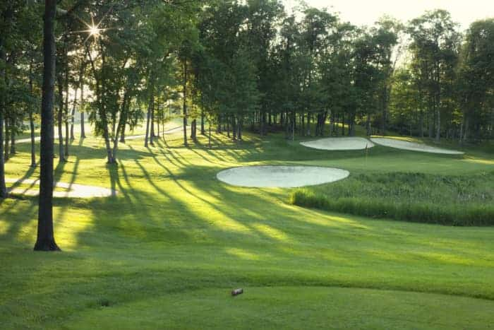 Sun peeking through the trees onto sand traps -- in addition the game, golfers will enjoy beautiful scenery at the best golf courses in Minnesota.
