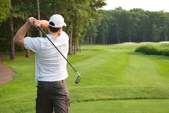 Male golfer swinging a golf club on a golf course.