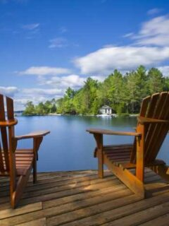 Wooden Adirondack chairs on a deck overlooking a lake