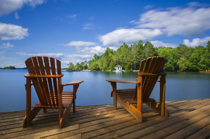 Two wooden chairs on a deck overlooking the lake.