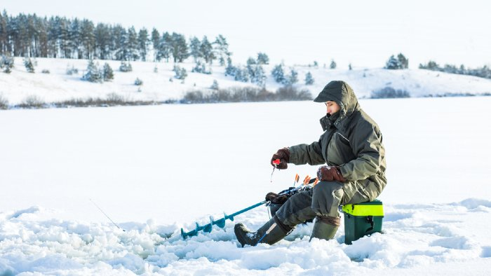 Man ice fishing with a tackle box, drill and pole.