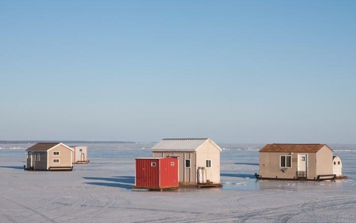 Ice houses on frozen lake