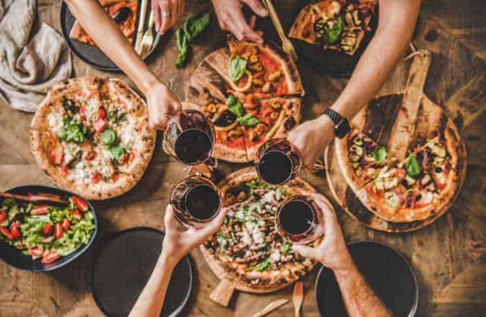 a group of friends toasting over an array of pizzas.