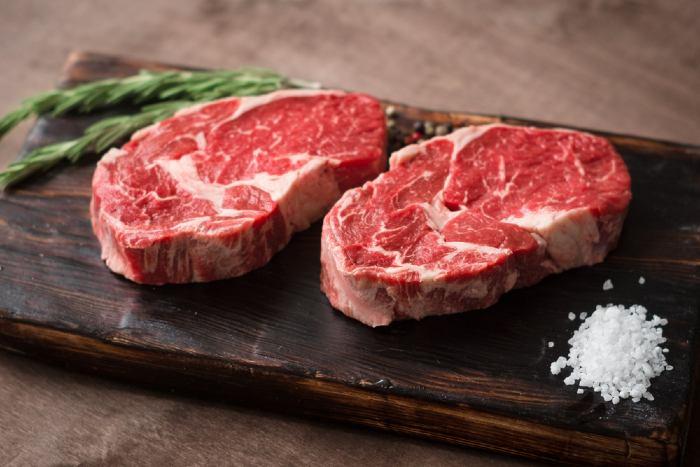 Raw rib-eye steaks on wooden board