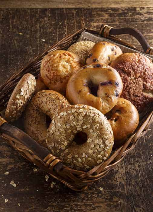 Fresh assorted bagels on a wooden table.