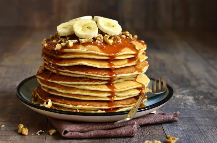 Plate served pancakes with bananas, nuts, and syrup.
