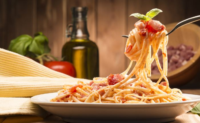 Spaghetti with amatriciana sauce on a wooden table.