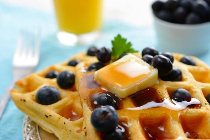 Waffles topped with butter, syrup, and blueberries.