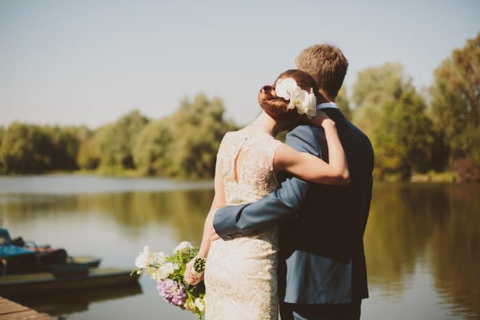 Bride and groom next to lake