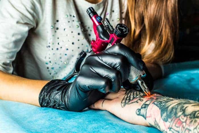 A tattoo artist draws the orange paint on the clients tattoo